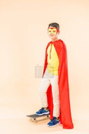 Photo pour Vue pleine longueur du garçon en masque et manteau rouge avec planche à roulettes sur rose - image libre de droit