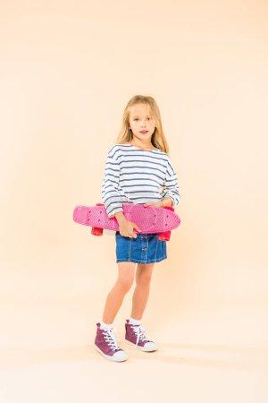 Photo pour Vue pleine longueur de l'enfant en denim chemise tenant skateboard sur rose - image libre de droit