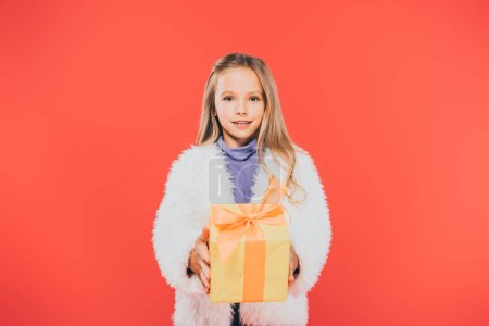 Photo for Front view of kid holding gift box isolated on red - Royalty Free Image