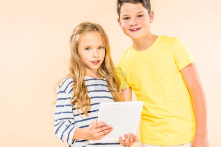 Photo for Two smiling kids using digital tablet isolated on pink - Royalty Free Image