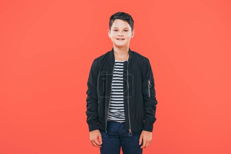 front view of smiling kid in jacket isolated on red
