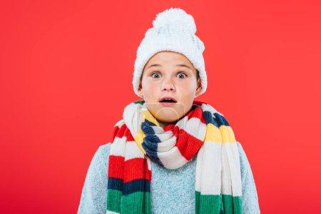 Photo pour Vue de face de l'enfant choqué en chapeau et écharpe isolé sur rouge - image libre de droit