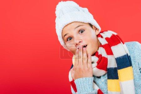 Photo pour Enfant surpris dans chapeau et écharpe couvrant la bouche avec la main isolée sur rouge - image libre de droit