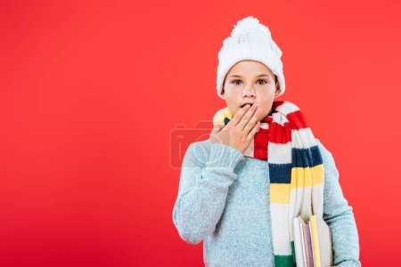 Photo for Front view of surprised kid in hat and scarf covering mouth with hand isolated on red - Royalty Free Image