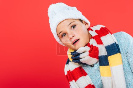 Photo for Shocked child in hat and scarf isolated on red - Royalty Free Image