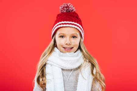 Photo for Front view of smiling kid in hat and scarf isolated on red - Royalty Free Image