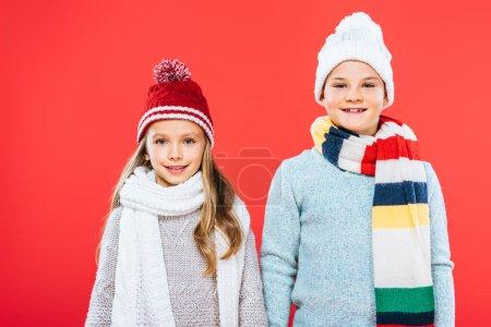Photo pour Vue avant de deux gosses dans des tenues d'hiver d'isolement sur le rouge - image libre de droit