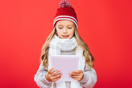 Photo pour Vue avant de l'enfant de sourire dans le chapeau et l'écharpe utilisant la tablette numérique d'isolement sur le rouge - image libre de droit