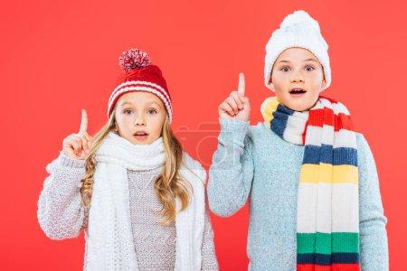 Photo pour Vue avant de deux enfants choqués dans des tenues d'hiver montrant des signes d'idée isolés sur le rouge - image libre de droit