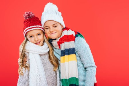 Photo for Two smiling kids in hats and scarfs embracing isolated on red - Royalty Free Image