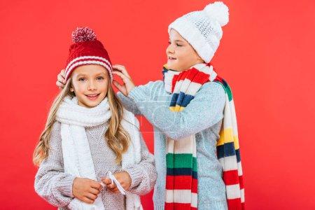 Photo pour Deux gosses de sourire dans des tenues d'hiver d'isolement sur le rouge - image libre de droit