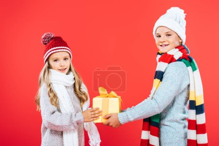 Photo for Two smiling kids in winter outfits with present isolated on red - Royalty Free Image