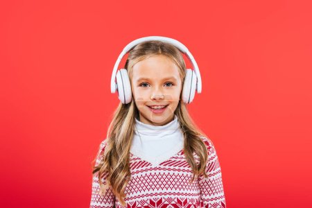 Photo for Front view of smiling kid in sweater listening music in headphones isolated on red - Royalty Free Image