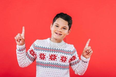 Photo pour Vue de face de l'enfant souriant en pull pointant avec les doigts isolés sur rouge - image libre de droit
