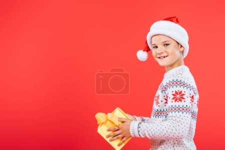 Photo for Smiling kid in santa hat holding present isolated on red - Royalty Free Image