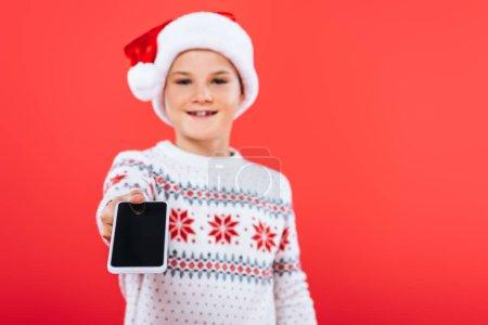 Selektiver Fokus eines lächelnden Kindes mit Weihnachtsmannmütze, das Smartphone mit leerem Bildschirm auf Rot isoliert hält