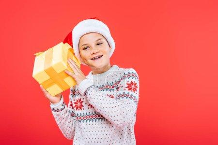 Photo pour Gosse de sourire dans le chapeau de santa retenant le présent d'isolement sur le rouge - image libre de droit