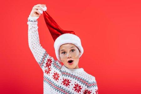 Photo pour Vue avant de l'enfant gai dans le chandail et le chapeau de santa d'isolement sur le rouge - image libre de droit
