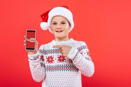 Photo pour Kiev, Ukraine - 9 septembre 2019: vue avant d'un enfant souriant dans un chapeau de Santa pointant du doigt sur un smartphone avec une application youtube à l'écran - image libre de droit