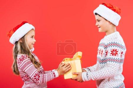 Photo pour Deux gosses de sourire dans des chapeaux de santa avec le présent regardant l'un l'autre isolé sur le rouge - image libre de droit