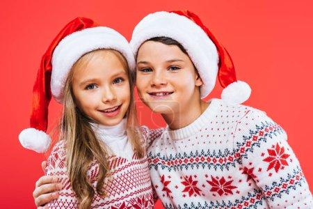 Photo pour Vue avant de deux gosses de sourire dans des chapeaux et des chandails de santa embrassant isolé sur le rouge - image libre de droit