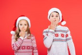 front view of two shocked kids in santa hats and sweaters covering mouths with hands isolated on red