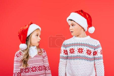 Photo pour Deux enfants surpris dans des chapeaux de santa regardant l'un l'autre isolé sur le rouge - image libre de droit
