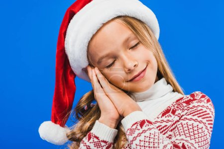 Photo for Cute kid in santa hat and sweater sleeping isolated on blue - Royalty Free Image