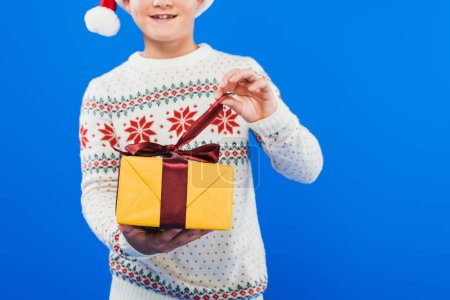 Photo for Cropped view of kid in santa hat and sweater holding gift isolated on blue - Royalty Free Image