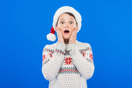 Photo pour Vue avant de l'enfant choqué dans le chapeau et le chandail de santa d'isolement sur le bleu - image libre de droit