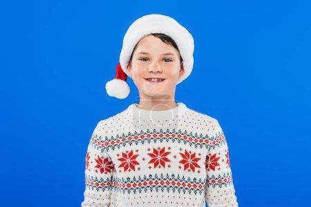 Photo pour Vue avant de l'enfant de sourire dans le chapeau et le chandail de santa d'isolement sur le bleu - image libre de droit