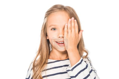 Photo for Front view of smiling kid covering eye with hand isolated on white - Royalty Free Image