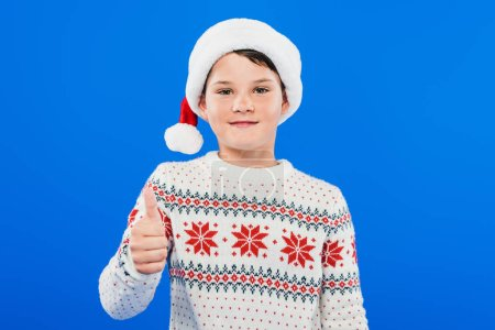 Photo for Front view of smiling kid in santa hat showing thumb up isolated on blue - Royalty Free Image