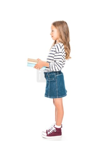 Photo for Side view of smiling kid with books isolated on white - Royalty Free Image