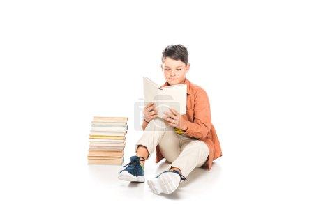 Photo pour Enfant concentré dans le livre de lecture occasionnel de tenue sur le blanc - image libre de droit