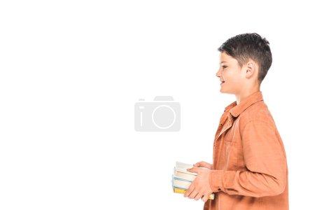 Photo pour Vue de côté de gosse de sourire dans les livres de fixation de chemise d'isolement sur le blanc - image libre de droit