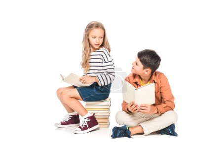 Photo for Two kids holding books and looking at each other on white - Royalty Free Image