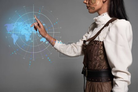 Photo pour Croquis d'une jeune femme au steampunk pointant du doigt à l'aide d'une carte numérique - image libre de droit