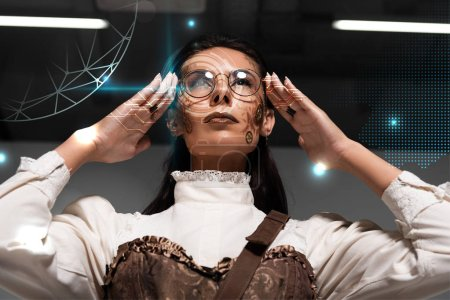 Photo pour Low angle view of steampunk woman with makeup touching glasses - image libre de droit