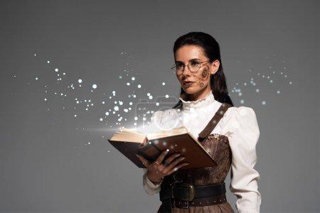 Photo pour Steampunk femme pensive en lunettes tenant un livre ouvert avec une illustration flamboyante de fée isolée sur gris - image libre de droit