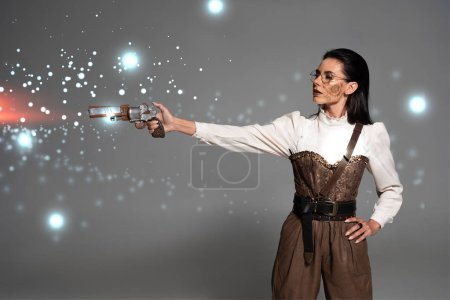 Photo pour Steampunk woman shooting from revolver with hand on hip on grey background with glowing illustration - image libre de droit