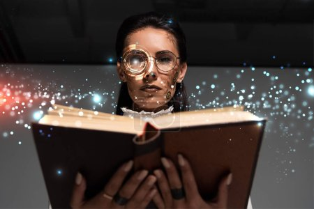 Photo pour Low angle view of steampunk woman in glasses reading book with glowing illustration above - image libre de droit