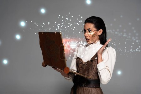 Photo pour Shocked steampunk woman in glasses using vintage laptop with glowing illustration isolated on grey - image libre de droit