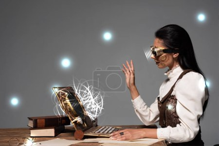 Photo for Steampunk woman in goggles waving hand during video chat with glowing digital illustration isolated on grey - Royalty Free Image