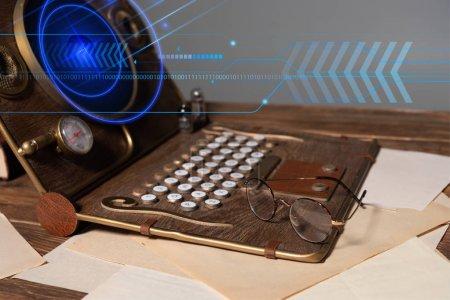 Photo pour Ordinateur portable steampunk avec illustration numérique, verres et documents sur table en bois isolés sur gris - image libre de droit