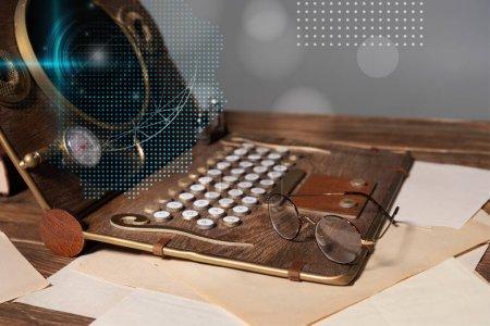 Photo pour Ordinateur portable avec illustration de données, lunettes et documents sur table en bois isolés sur gris - image libre de droit