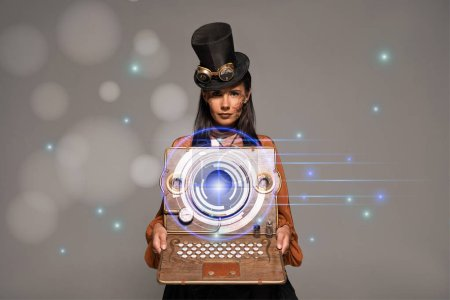 Photo pour Steampunk woman in top hat with goggles showing vintage laptop with glowing digital illustration isolated on grey - image libre de droit