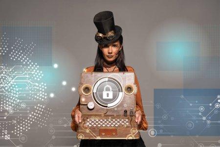 Photo pour Steampunk femme au chapeau de haut avec lunettes montrant un ordinateur portable vintage avec illustration de sécurité Internet isolée sur gris - image libre de droit