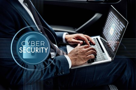 Photo for Partial view of african american businessman using laptop in car with cyber security illustration - Royalty Free Image