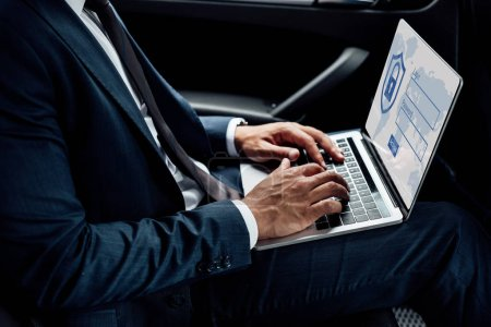 Photo for Partial view of african american businessman using laptop with internet security illustration in car - Royalty Free Image